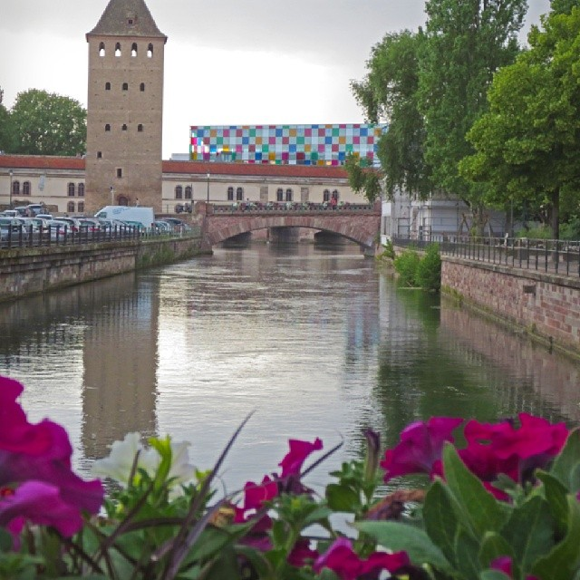 Photo: View from the Rue des Moulins on #Petit #France onto the colourful #facade of the #Musée d'Art moderne et contemporain. #Strasbourg #canal #flowers #architecture #urban #purple #pink
